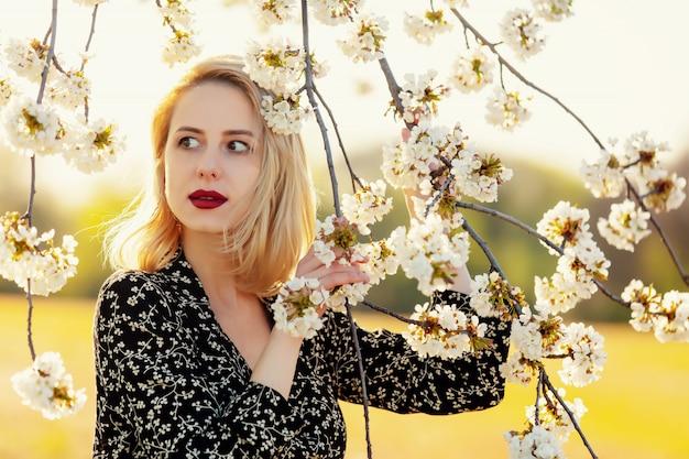 Blondemeisje dichtbij bloeiende boom bij platteland in zonsondergang