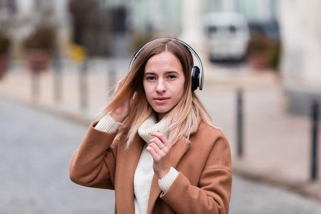 Blondemeisje die aan muziek op hoofdtelefoons luisteren