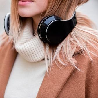 Blondemeisje die aan muziek op hoofdtelefoonsclose-up luisteren