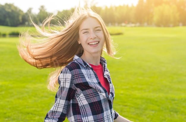 Blondemeisje die de camera op een zonnige dag bekijken