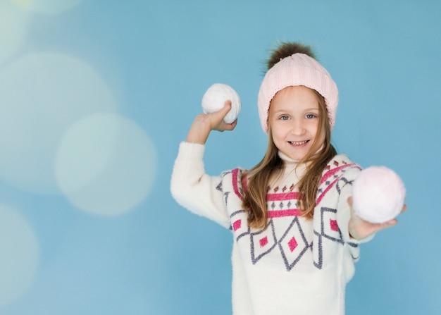 Blondemeisje die een sneeuwbal voorbereidingen treffen te werpen