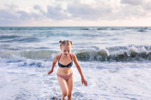 Blondemeisje die en op het strand op blauwe overzeese kust in de zomervakantie in de dagtijd lopen springen.