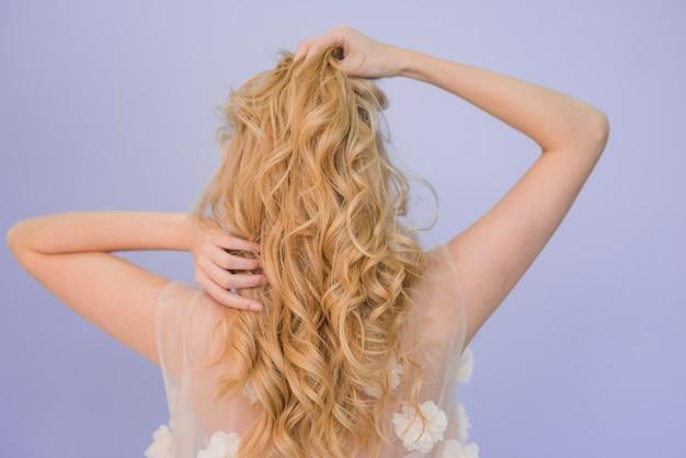 Blondemeisje die haar haar behandelen