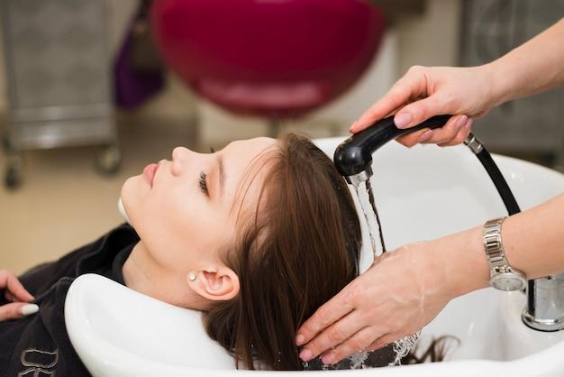 Blondemeisje die haar haar krijgen gewassen