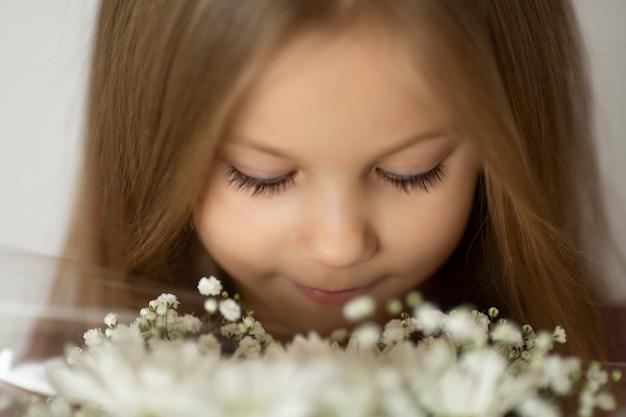 Blondemeisje die met gesloten ogen van een wit boeket van wilde bloemen genieten