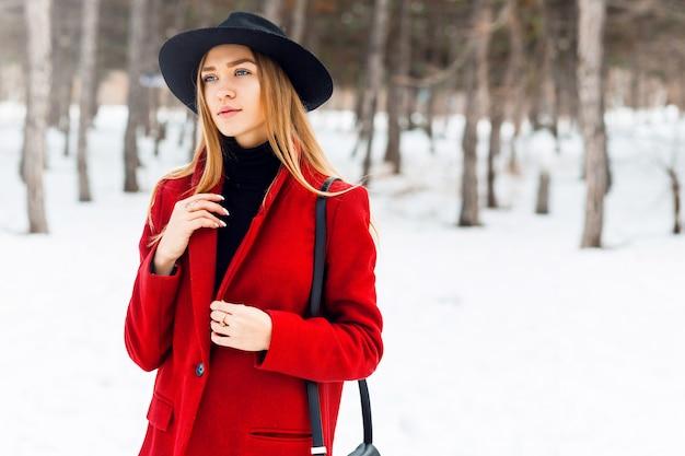 Blondemeisje die rode laag op een sneeuwgebied dragen
