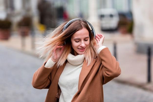 Blondemeisje die van muziek op hoofdtelefoons genieten
