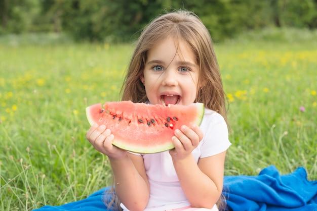 Blondemeisje die watermeloenplak in het park eten