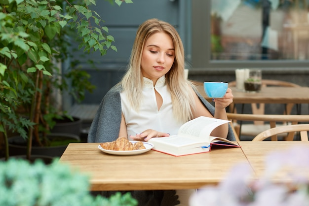 Blondemeisje het drinken koffie terwijl het lezen van een boekzitting op de zitkamer van het koffie.