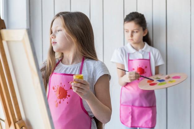 Blondemeisje het schilderen op de schildersezel en haar vriend die zich achter achtergrond bevinden