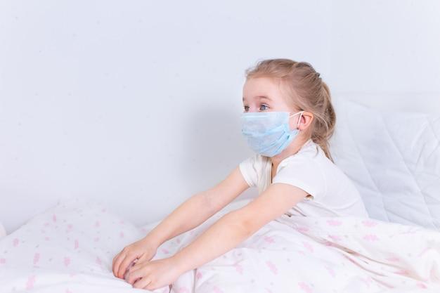 Blondemeisje in beschermend medisch masker dat in wit bed in een witte ruimte ligt.