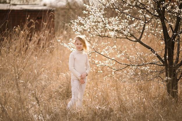 Blondemeisje in de bloesemtuin. de lenteachtergrond met witte bloem