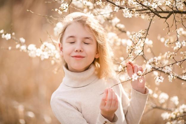 Blondemeisje in de bloesemtuin. lente achtergrond met witte bloem