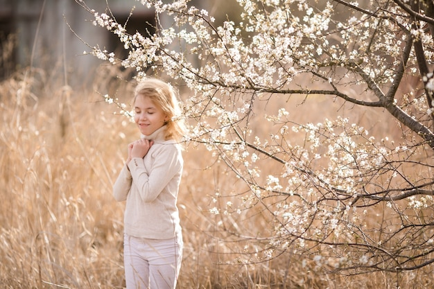 Blondemeisje in de bloesemtuin.