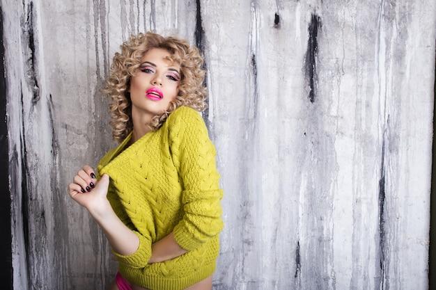 Blondemeisje in een gele sweater en roze damesslipjes