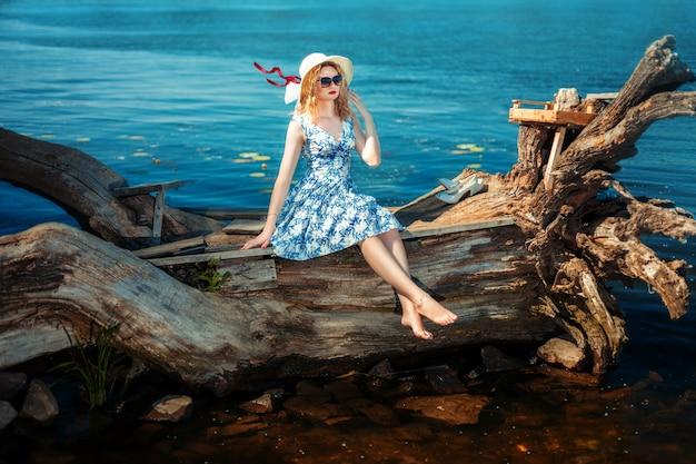 Blondemeisje in een hoed en zonnebril die op drijfhout op riverbank zitten. ze legde haar hand op haar gezicht