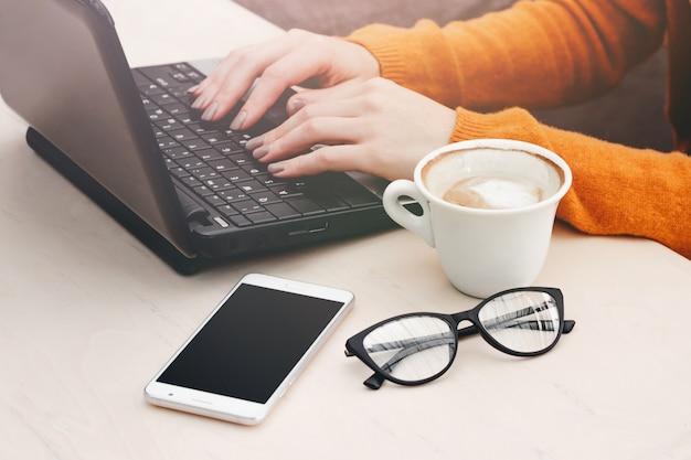 Blondemeisje in een koffie met laptop en een koffie. jong meisje die freelancer aan laptop werken