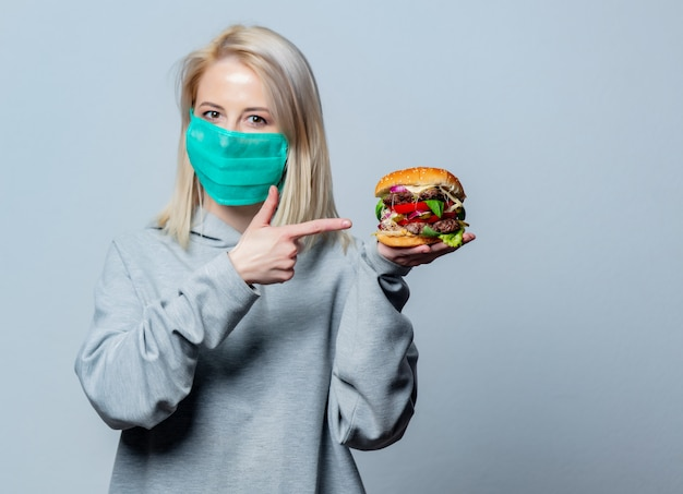 Blondemeisje in gezichtsmasker met hamburger op witte ruimte