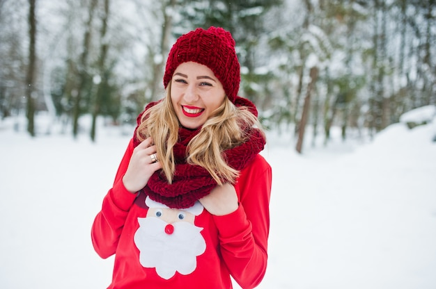 Blondemeisje in het rode sjaal, hoed en santas sweater stellen bij park op de winterdag.