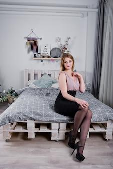 Blondemeisje in kleding die op bed dichtbij nieuwe jaarboom wordt gesteld met het decor van kerstmisgiften in witte ruimte.