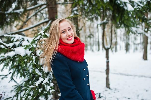 Blondemeisje in rode sjaal en laag die bij park op de winterdag lopen.