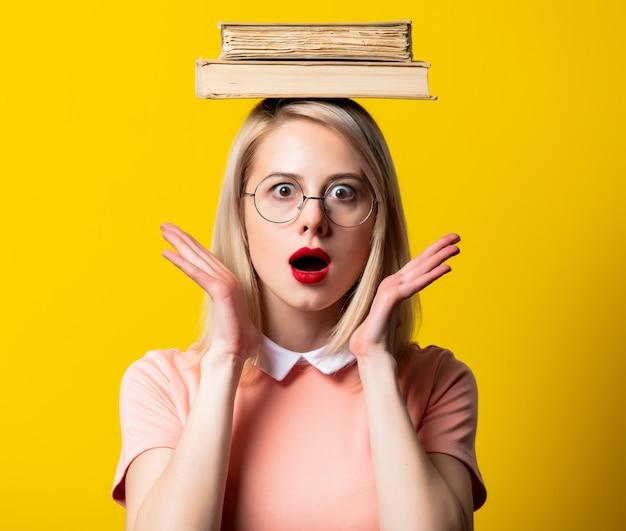 Blondemeisje in roze kleding en glazen met boeken op gele ruimte