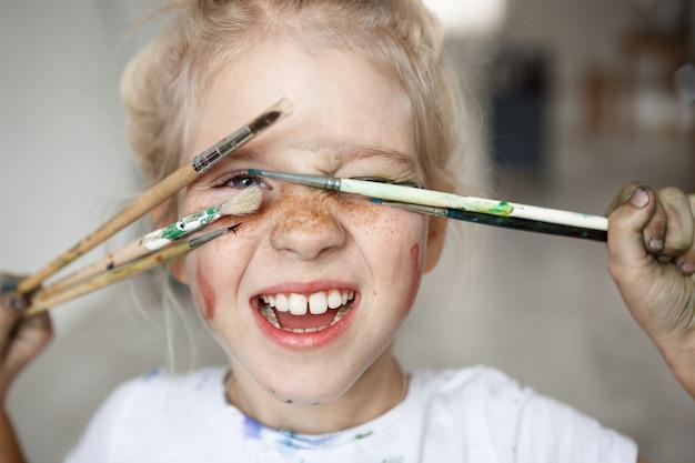 Blondemeisje in speelse stemming met verf op haar sproeterig gezicht en blauwe ogen die haar gezicht behandelen met borstels