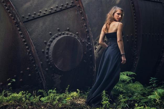 Blondemeisje in zwarte kleding bij een oude verlaten fabriek. steampunk