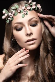 Blondemeisje met bloemen in haar haar op donkere muur