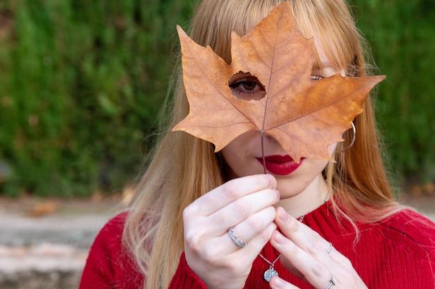 Blondemeisje met geschilderde lippen en rode sweater die één oog bedekken met een boomblad.