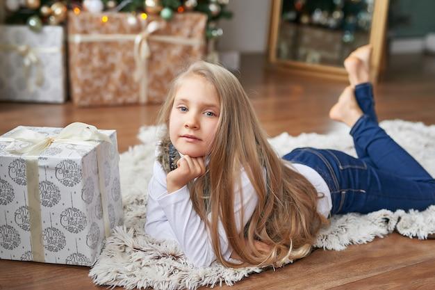 Blondemeisje met giften in het binnenland van het nieuwjaar