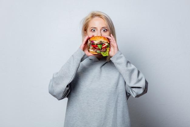 Blondemeisje met hamburger op witte ruimte