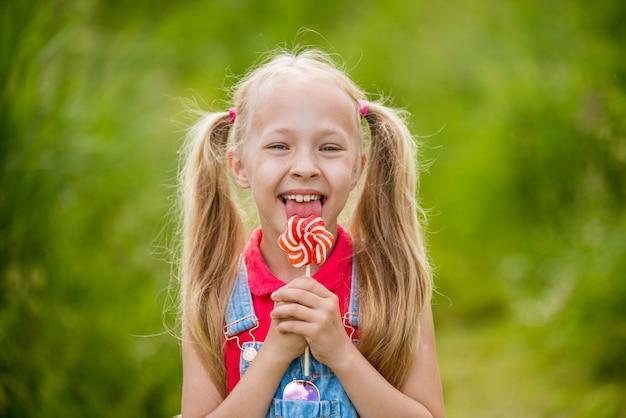 Blondemeisje met lang haar en suikergoed op een stok