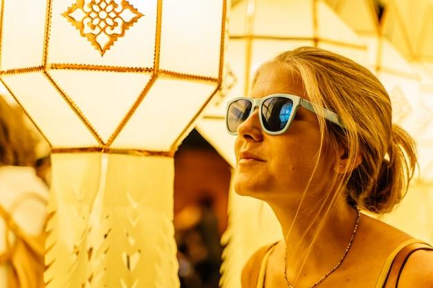 Blondemeisje met zonnebril door chinese lantaarns bij nacht wordt omringd die
