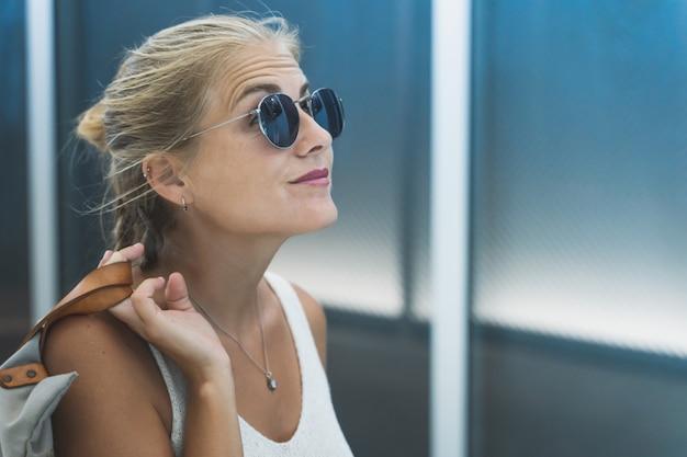 Blondemeisje met zonnebril en een wit mouwloos onderhemd die een zak met haar hand op haar rug houden die de hemel voor een modern gebouw onder ogen zien