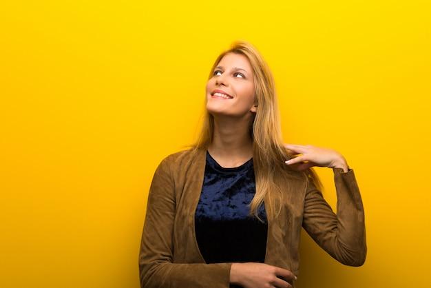 Blondemeisje op trillende gele achtergrond die een idee denken terwijl het krassen van hoofd