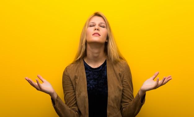 Blondemeisje op trillende gele die achtergrond door een slechte situatie wordt gefrustreerd