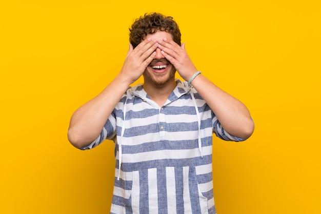 Blondemens die over gele muur ogen behandelen door handen. verrast om te zien wat er gaat gebeuren