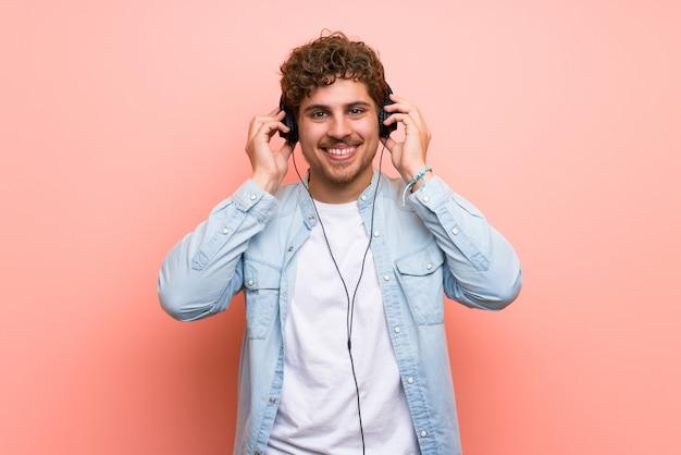 Blondemens die over roze muur aan muziek met hoofdtelefoons luisteren