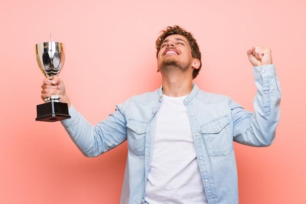Blondemens die over roze muur een trofee houden