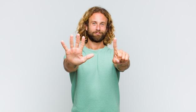 Blondemens die vriendelijk glimlacht kijkt, nummer zes of zesde met vooruit hand toont, aftellend