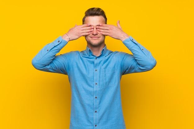 Blondemens over geïsoleerde gele muur die ogen behandelt door handen