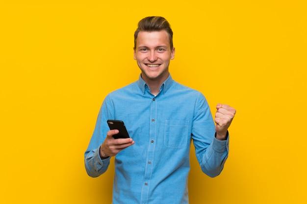 Blondemens over geïsoleerde gele muur met telefoon in overwinningspositie