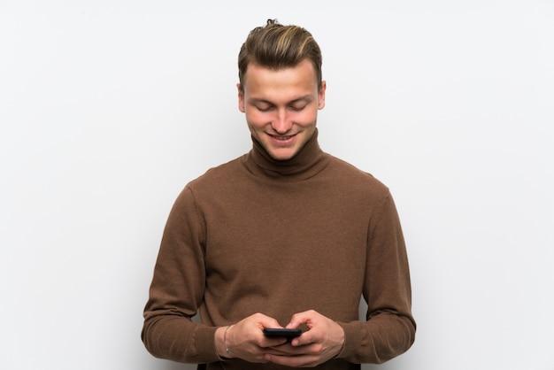 Blondemens over geïsoleerde witte muur die een bericht met mobiel verzenden