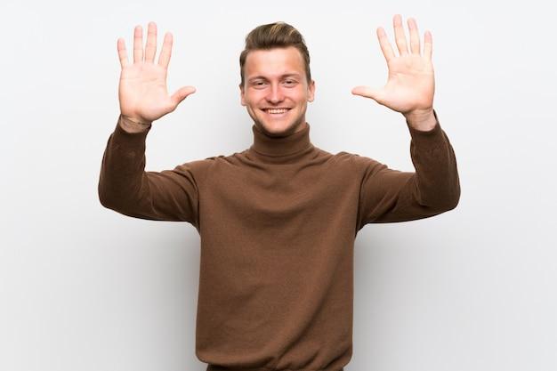 Blondemens over geïsoleerde witte muur die tien met vingers telt