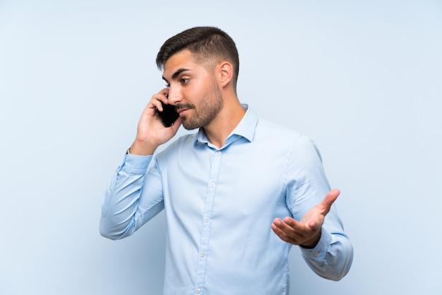 Blondemens over geïsoleerde witte muur met telefoon in overwinningspositie