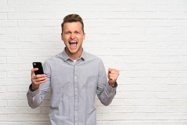 Blondemens over witte bakstenen muur met telefoon in overwinningspositie