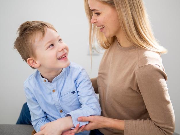 Blondemoeder en jonge jongen die bij elkaar glimlachen