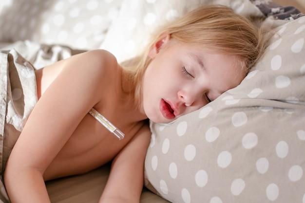Blondeslaapkind met klinische thermometer