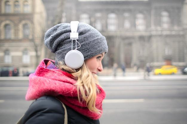 Blondevrouw die aan muziek op hoofdtelefoons luisteren